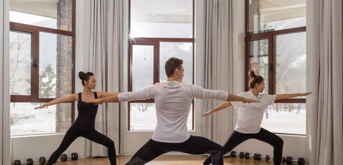 Club Med Peisey - Vallandry, en France - Un groupe de gens profite d'une séance de yoga, entourées de baies vitrées
