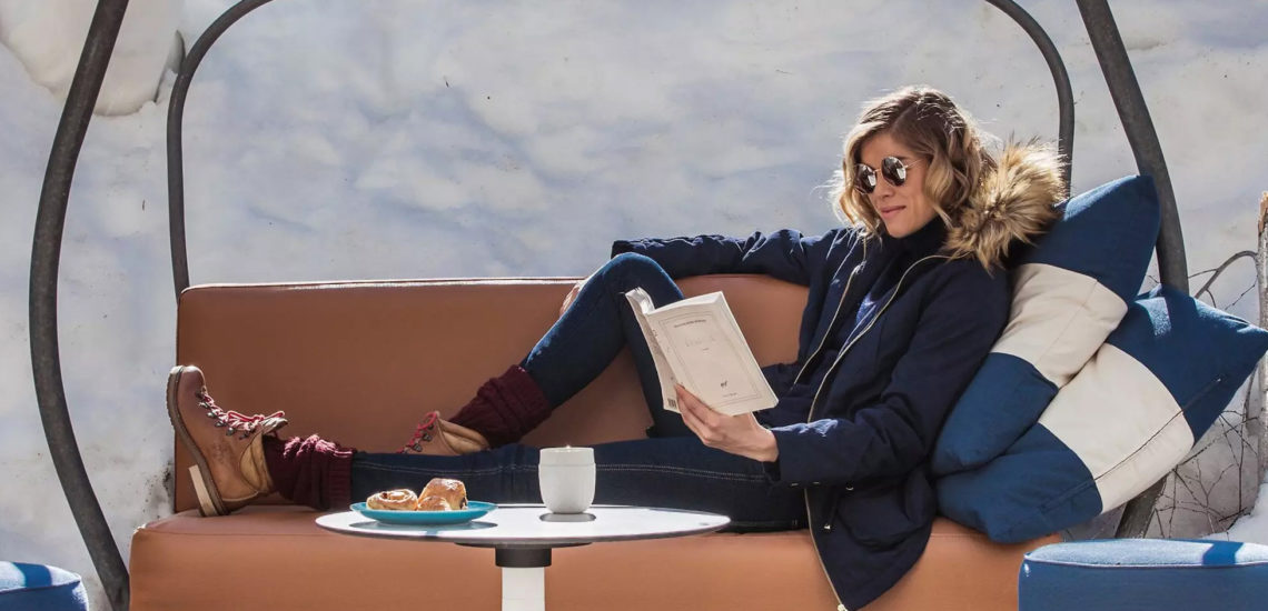 Club Med Peisey - Vallandry, en France - Une femme est assis sur un banc et lis un livre, au Snow Motion