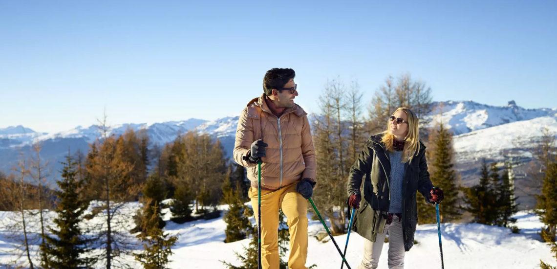 Club Med Peisey - Vallandry, en France - Un couple pratique un sport d'hiver, dans la forêt environnante du Village