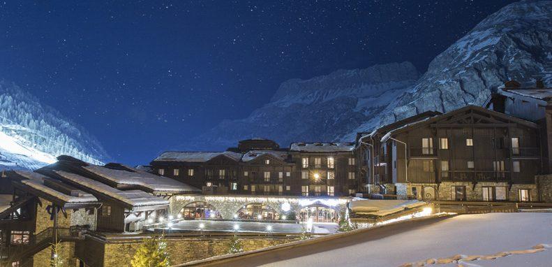 Club Med Val d'Isère, en France - Vue extérieure  avec la montagne en arrière-plan la nuit.