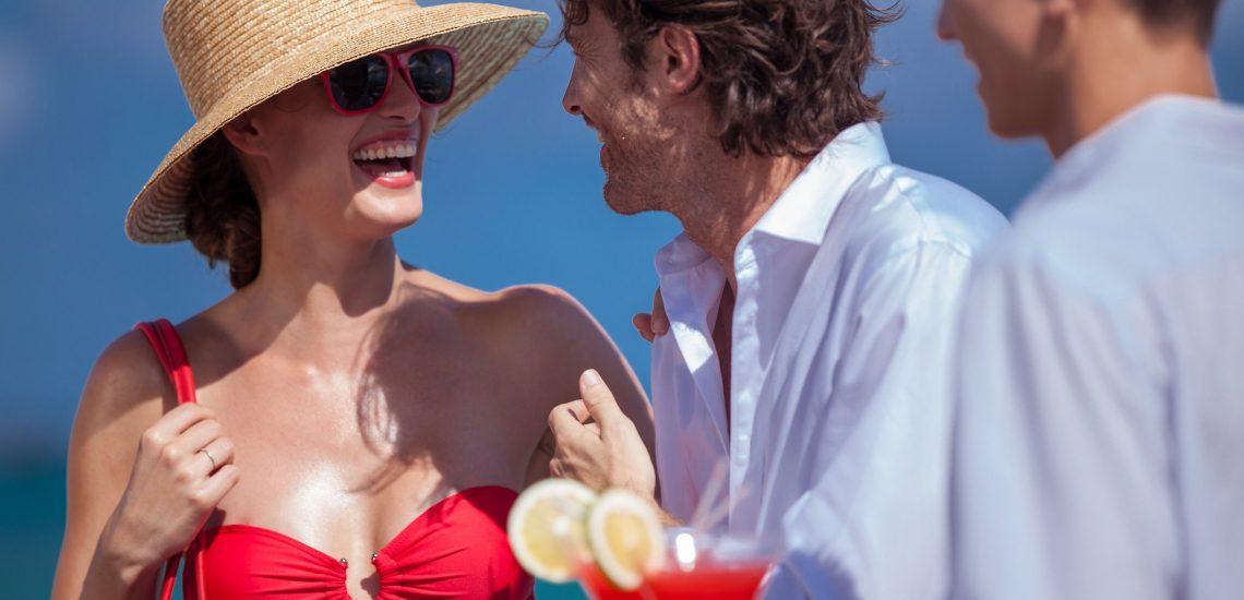 Club Med Miches Playa Esmeralda, en République Dominicaine - Image d'une femme et d'un homme souriant en habit de plage avec des cocktails