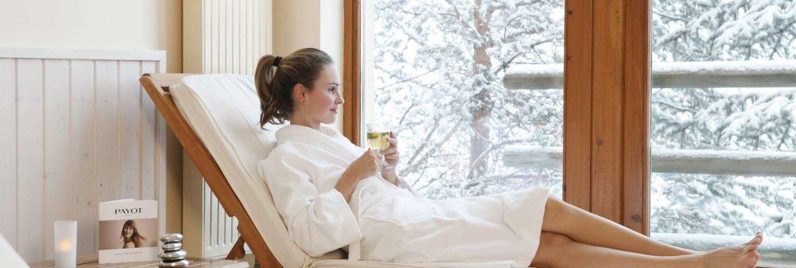 Image d'une femme en peignoir allongée sur un transat en intérieur avec vue sur le paysage enneigé
