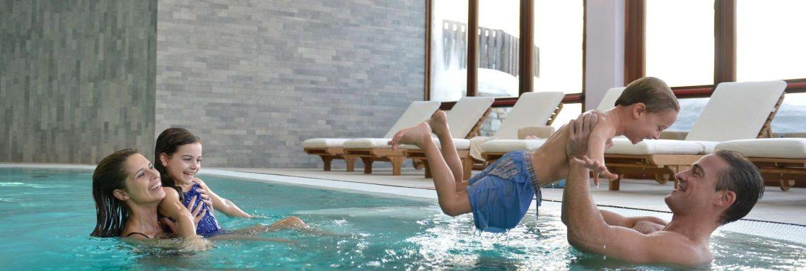 Image d'une famille jouant dans la piscine intérieure