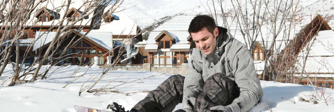 Image d'un homme assis dans la neige avec une planche de snowboard