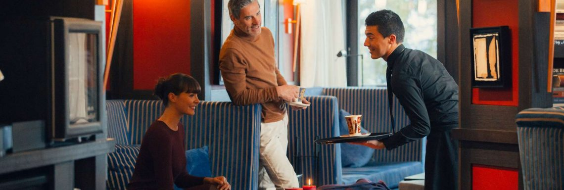 Club Med Valmorel, en France - Image de deux personnes s'adressant au serveur dans l'espace lounge