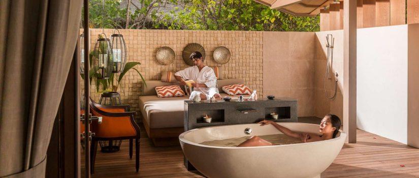 Club Med Villas de Finolhu, aux Maldives - Un couple profite de la salle de bain extérieure privée de leur location.