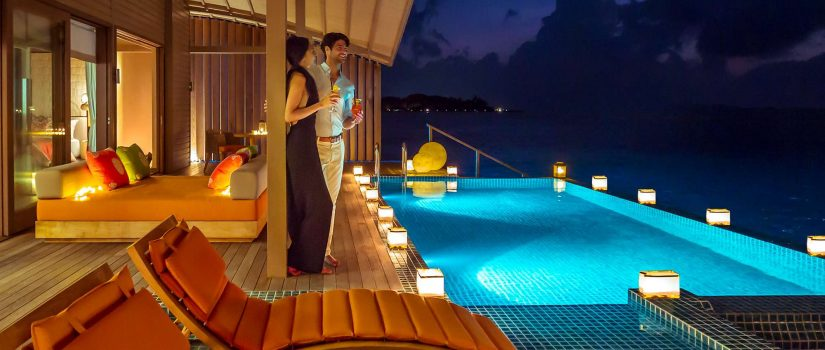 Club Med Villas de Finolhu, aux Maldives - Un couple devant leurs piscine privée, en soirée.