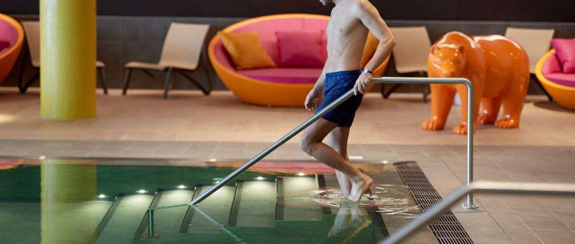 Image d'un homme descendant les marches de la piscine d'intérieur