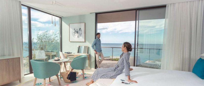 Image d'un couple dans une chambre double avec vue sur la mer
