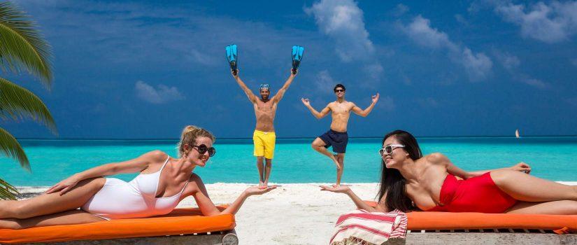 Club Med Kani, aux Maldives - Quatre personnes profitent de la plage sur des chaises longues.