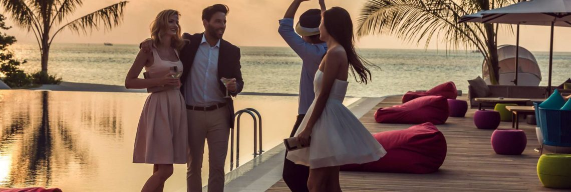 Deux couples devant la piscine du Club Med au coucher de soleil