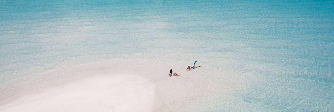 Photo aérienne de deux personnes, seules sur la plage de la lagune