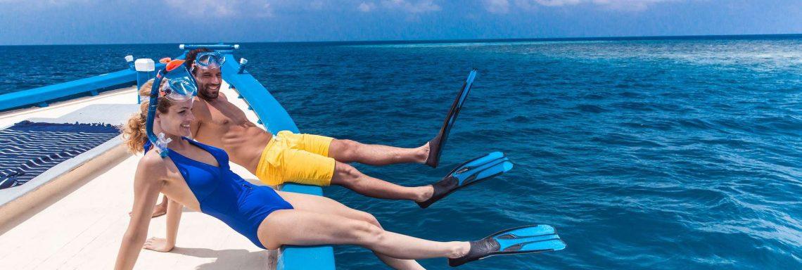 Photo d'un couple sur un bateau s'apprêtant à plonger avec masques et tuba