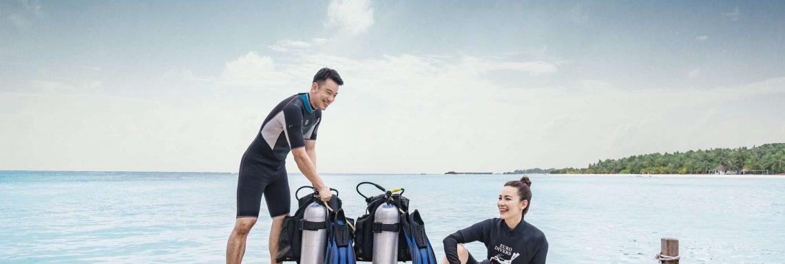 Photo de deux personnes souriantes s'apprêtant à plonger devant l'océan