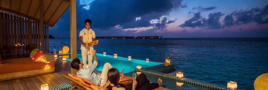 Club Med Villas de FInolhu, aux Maldives - Photo d'un couple sur des transat devant la piscine et l'océan Indien