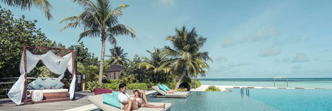 Club Med Villas de FInolhu, aux Maldives - Photo d'un couple sur un sofa sur la piscine à débordements devant la lagune