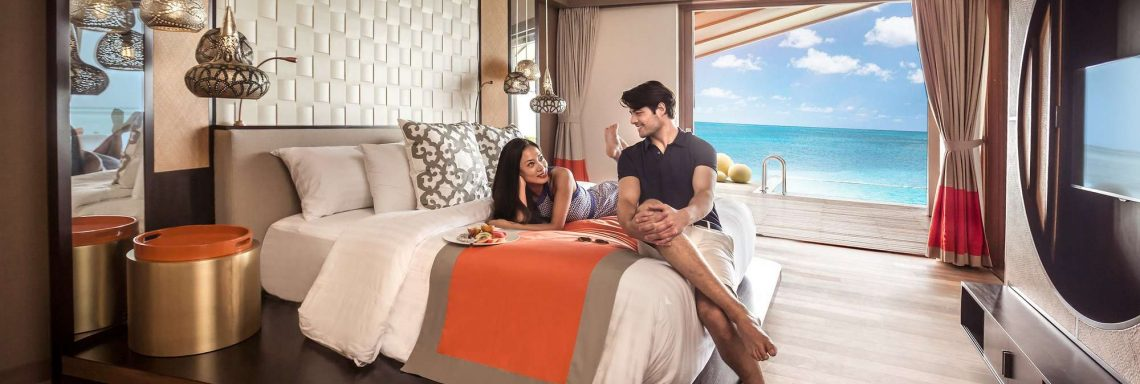 Club Med Villas de FInolhu, aux Maldives - Photo d'un couple dans une chambre d'une villa avec vue sur la lagune