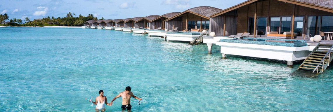 Club Med Villas de FInolhu, aux Maldives - Un couple se baignant dans la lagune devant une villa