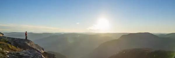 Photo d'une personne perchée sur un rocher devant un paysage de montagne