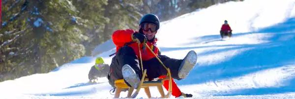 Photo de trois personnes descendant une piste de ski sur des luges