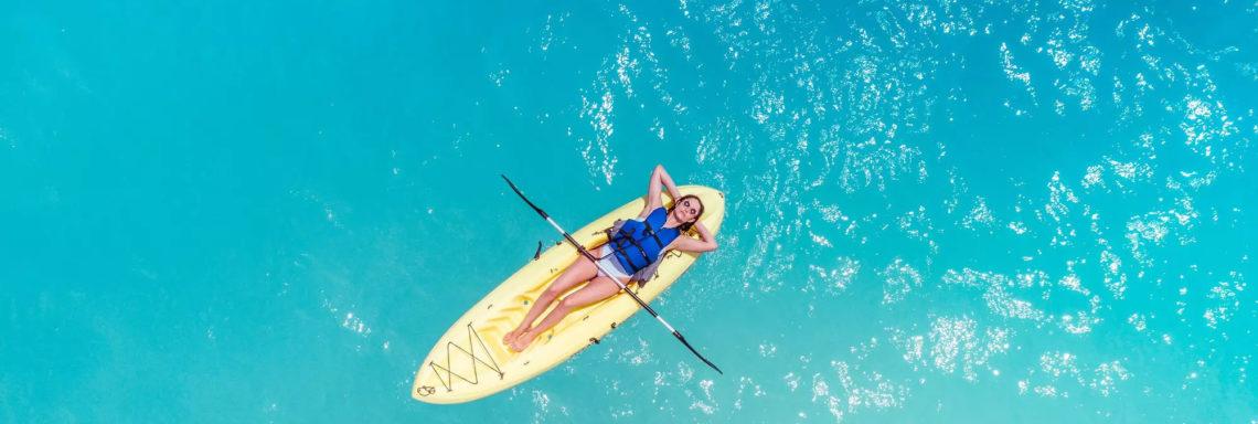 Club Med Columbus Isle, au Bahamas - Une femme est couchée sur un kayak, en pleine mer.