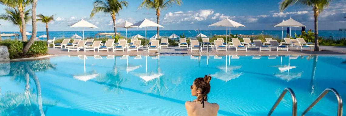 Club Med Columbus Isle, au Bahamas - Une femme est assise sur le bord de la piscine, du complexe, face à la mer