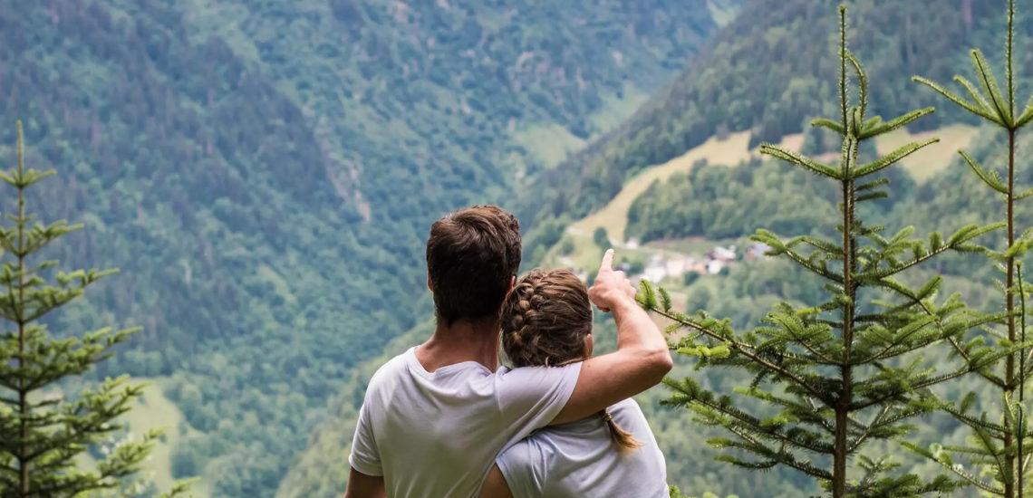 Club Med Samoëns, en France - Un couple profite, en pic de montagne, de la vue offerte de la vallée sa