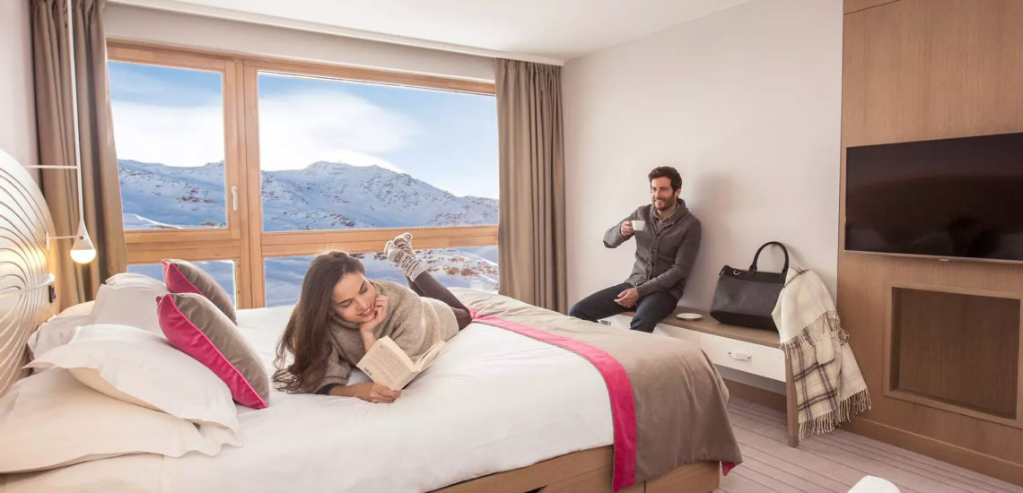 Club Med Val Thorens Sensations, France - Une femme est allongée sur un lit et son mari la regarde assis sur un banc
