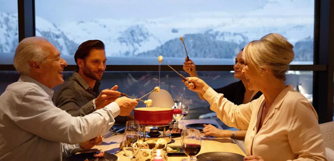 Club Med Tignes Val Claret, France - Image d'un groupe de personne qui mange une fondue avec vue sur la montagne en arrière plan